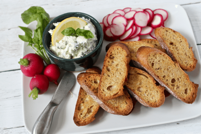 Cheese and herb spread served on a platter for an appetizer