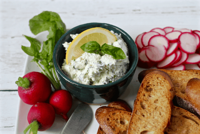 Cheese and herb spread served in a small green dish with baguette slices