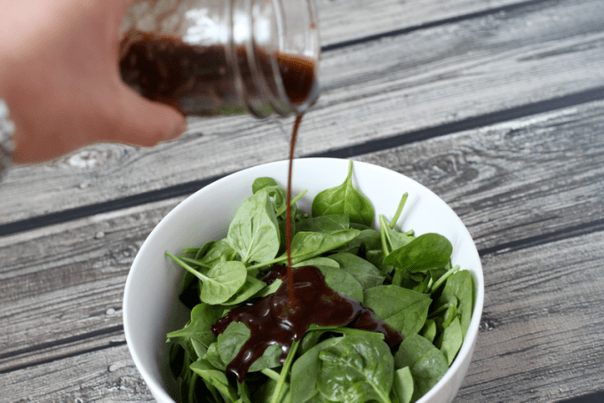 Simple spinach salad in a white bowl with balsamic vinaigrette being poured on top