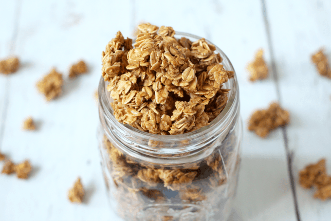 Homemade peanut butter granola in a glass mason jar and scattered on a counter