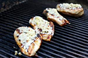 Chicken breasts on the grill topped with cheese