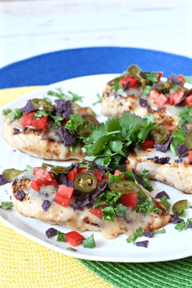 Cheesy fiesta grilled chicken served on a plate with cilantro and toppings