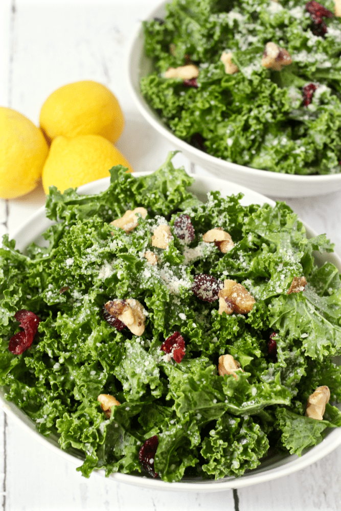This fresh citrus kale salad is light and lemony with crunchy walnuts, tart dried cranberries, Parmesan cheese and a hint of sweetness! #kale #kalesalad #healthysalad #sidesalad #saladrecipes