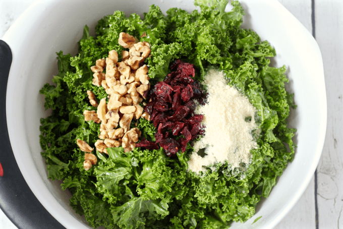 Citrus kale salad with walnuts, dried cranberries and Parmesan cheese in a white bowl