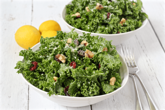 Citrus kale salad with walnuts, dried cranberries and Parmesan cheese served in white bowls