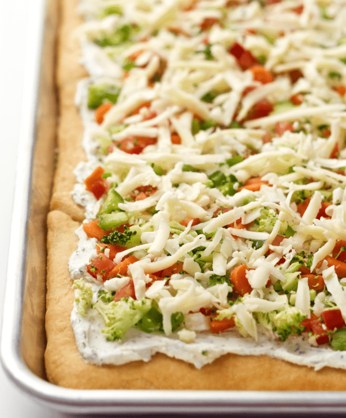 Easy vegetable squares are crescent rolls spread with a cream cheese mixture, sprinkled with veggies and cheddar and served cold for a great veggie pizza appetizer! #appetizer #gameday #holidays #pizza #easyrecipe