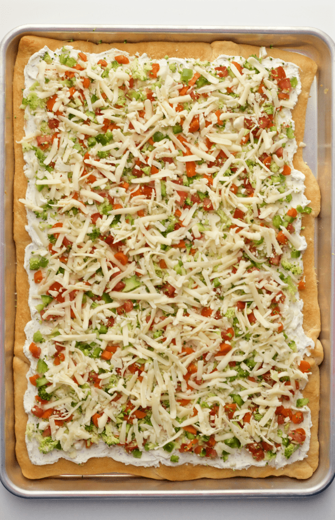 Easy vegetable squares on a large baking sheet covered with chopped veggies and shredded cheese