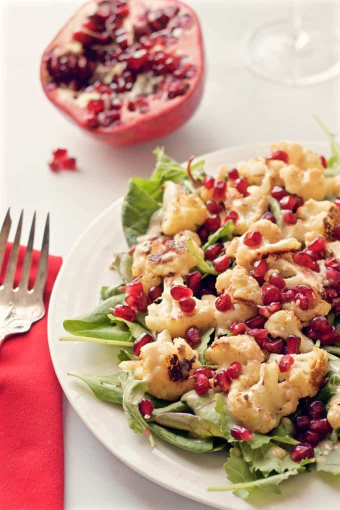 Baby kale and roasted cauliflower salad sprinkled with pomegranate seeds and drizzled with a creamy tahini dressing - so flavorful!   FamilyFoodontheTable.com