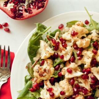 Baby kale and roasted cauliflower salad sprinkled with pomegranate seeds and drizzled with a creamy tahini dressing | FamilyFoodontheTable.com