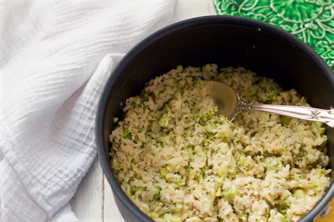 Healthy brown rice recipe with broccoli and cheddar cheese mixed in, being served from a large pot
