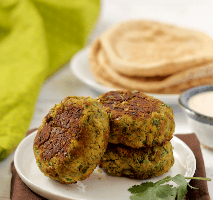 Easy baked falafel - these have a crispy exterior and soft inside with bright, fresh herbs. Also includes an easy tahini sauce to serve them with! | FamilyFoodontheTable.com