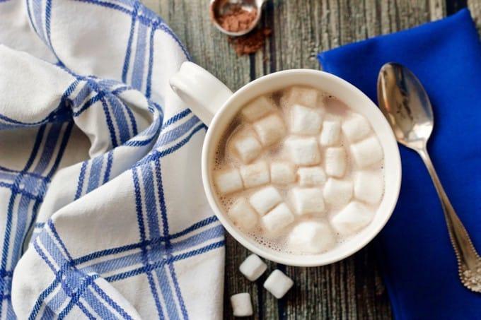 A white coffee mug with hot cocoa and mini marshmallows