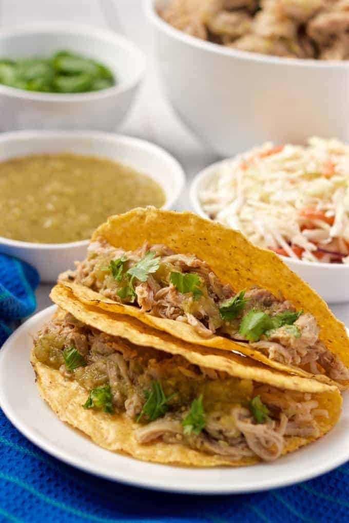 Slow cooker salsa verde shredded pork piled into some tacos with toppings in the background
