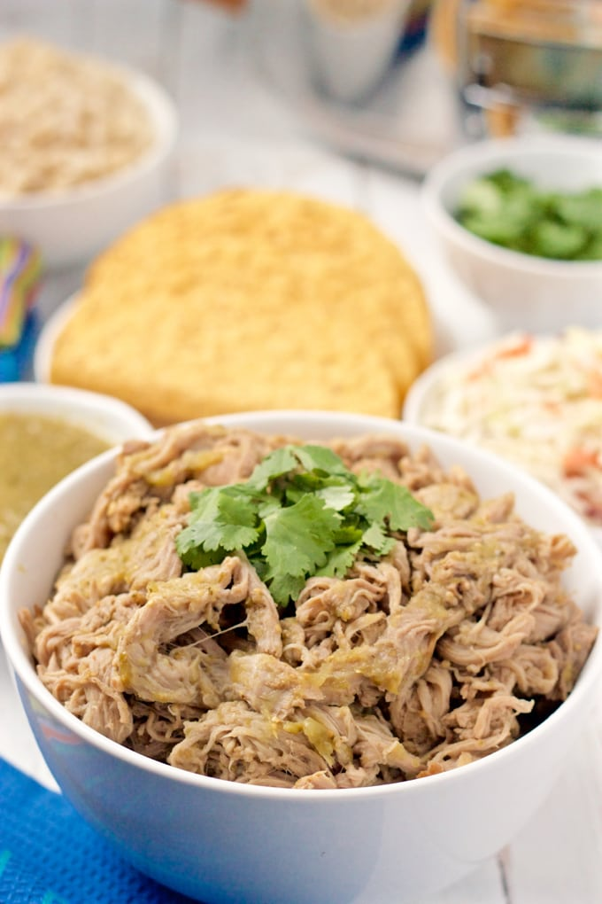 Slow cooker salsa verde shredded pork in a white serving bowl with cilantro on top