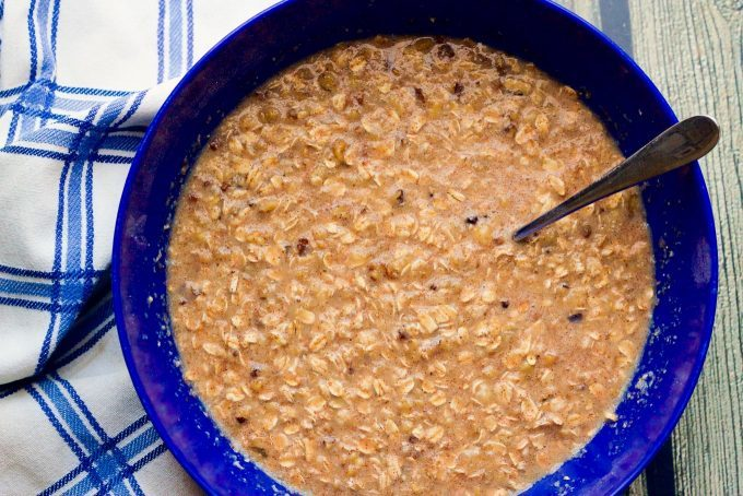 Batter for baked oatmeal in a large blue bowl