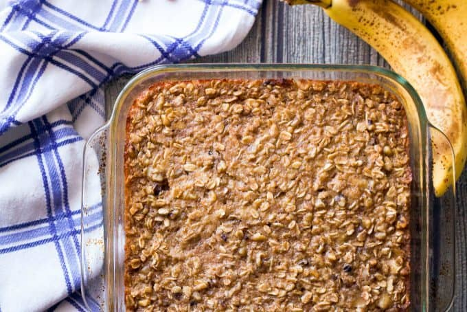 Baked oatmeal in a glass pan with bananas on the counter nearby