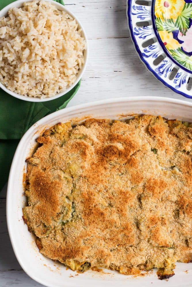 A baked casserole dish in a white pan with a golden brown topping a bowl of brown rice