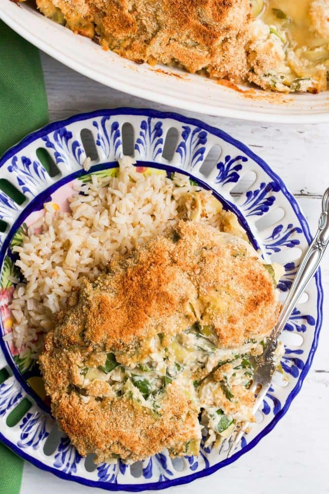 Creamy spinach artichoke baked chicken served on a blue and white plate over a bed of rice