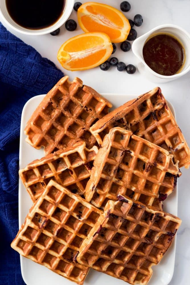A platter of waffles being served with maple syrup, blueberries, oranges and coffee nearby