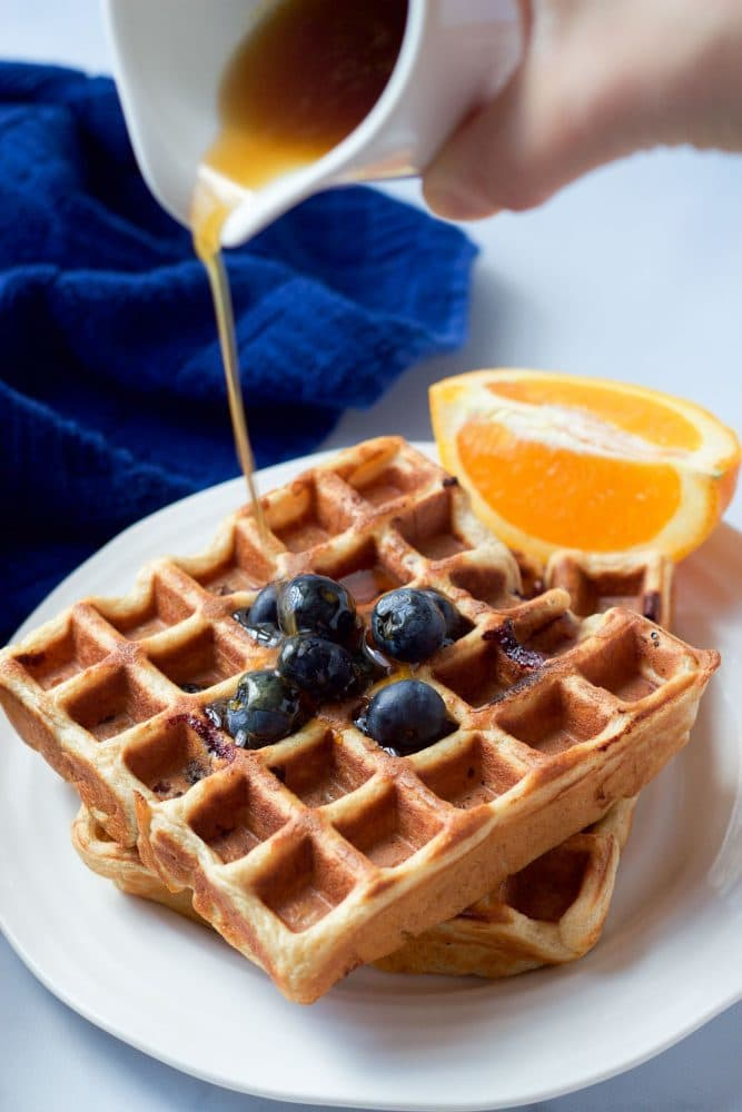 Maple syrup being drizzled over whole wheat waffles with blueberries on top