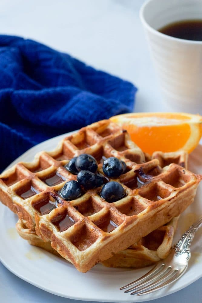 Two healthy blueberry waffles served on a plate with maple syrup and extra blueberries