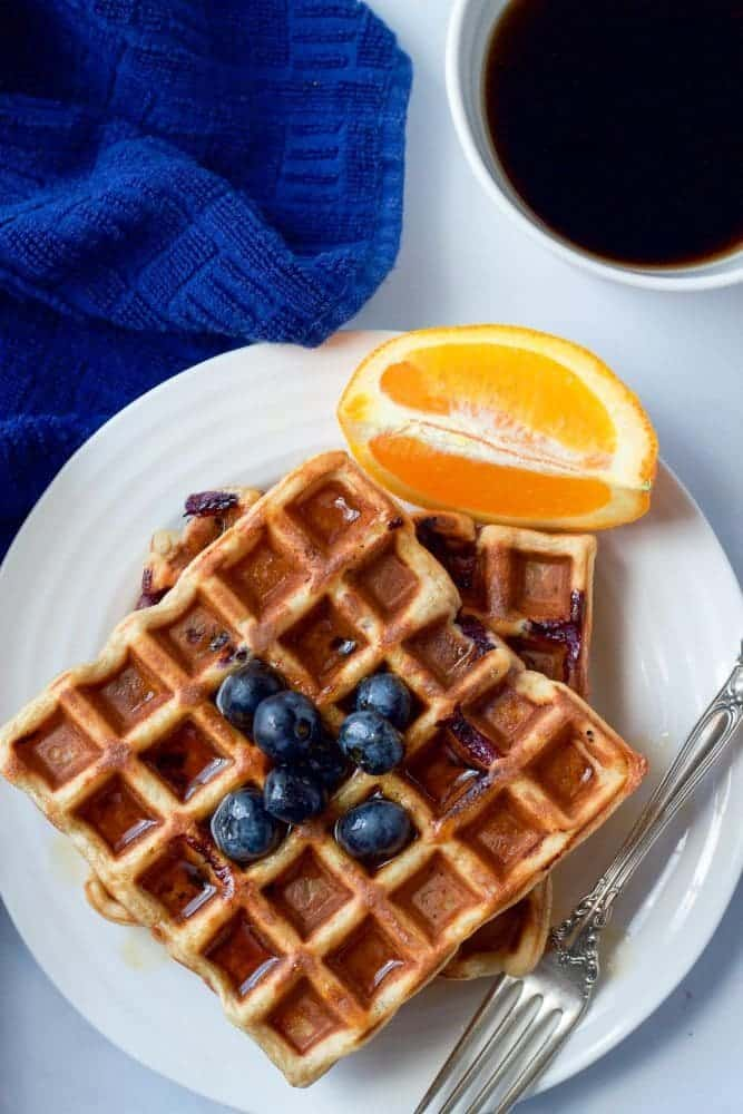 A stack of two blueberry waffles served on a plate with orange slices and fresh blueberries