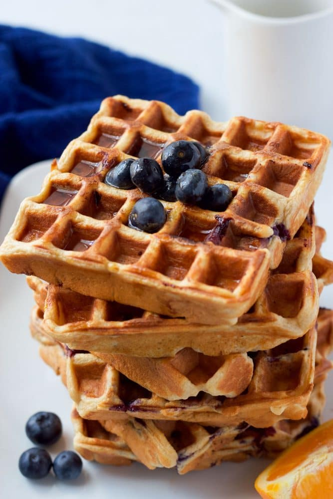 A tall stack of blueberry waffles with extra blueberries on top and nearby