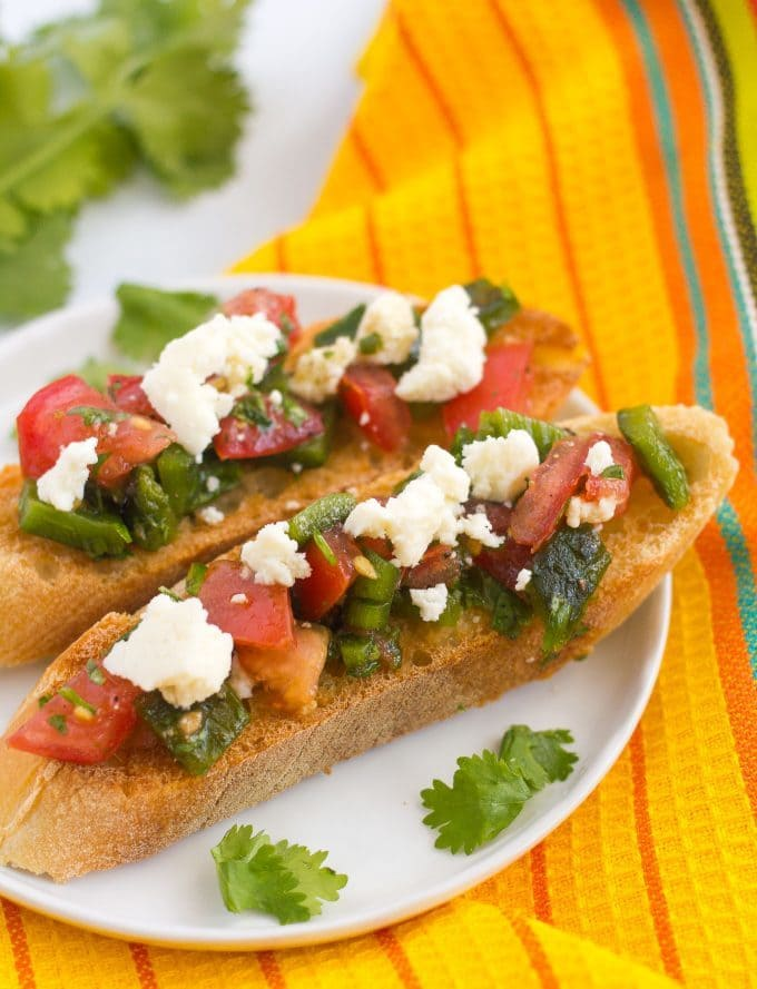 A couple of pieces of Mexican style bruschetta served on a plate