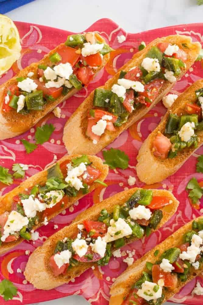 Bruschetta appetizer served with roasted poblanos, jalapenos, cilantro and queso fresco