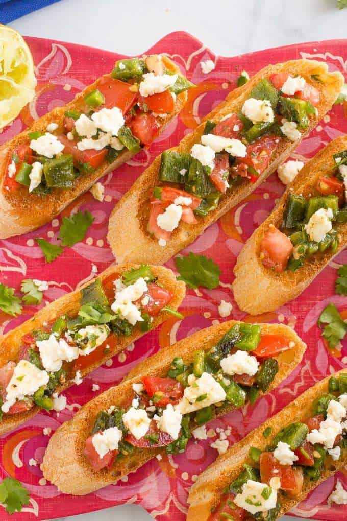 An easy Mexican-style bruschetta appetizer with roasted poblano peppers, jalapeno and queso fresco cheese | FamilyFoodontheTable.com