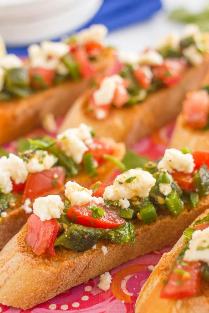 Close up of toasted bruschetta with poblanos, tomatoes, jalapenos and toppings