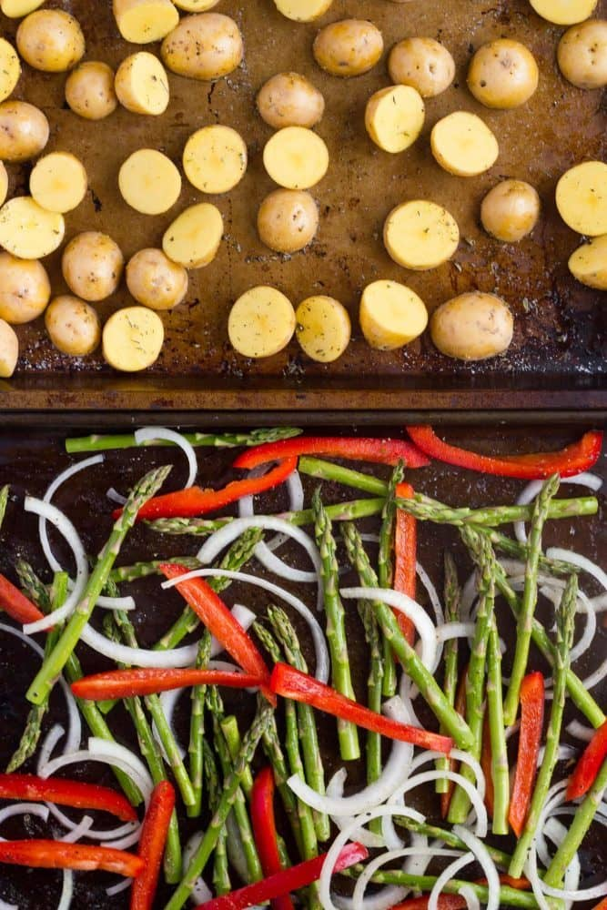 Sheet pans ready to roast of baby potatoes and fresh vegetables