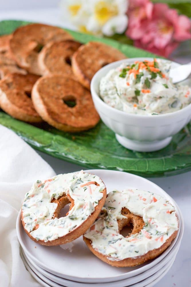 A bagel spread with veggie cream cheese served on a white plate