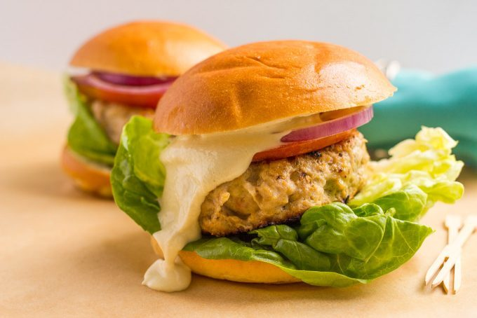Cheddar chicken burgers served with toppings and a creamy sauce