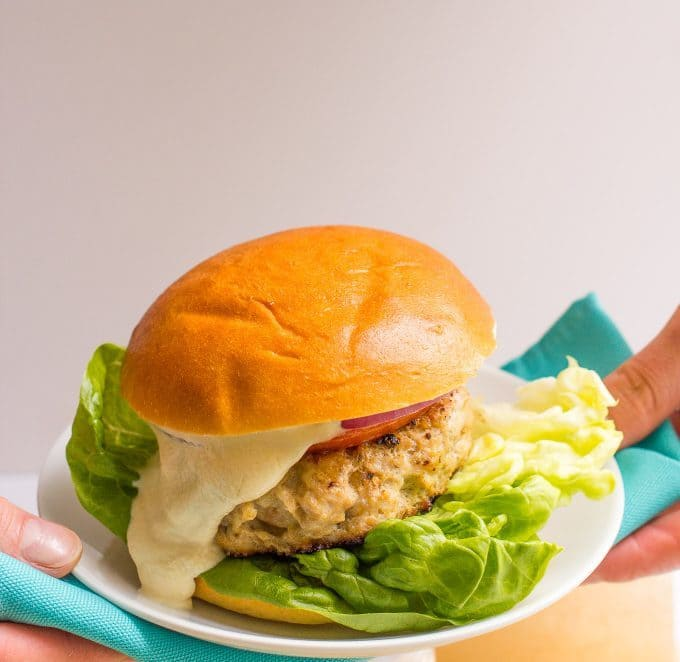 Ground chicken burger served on a bun with lettuce and tomato and a creamy sauce