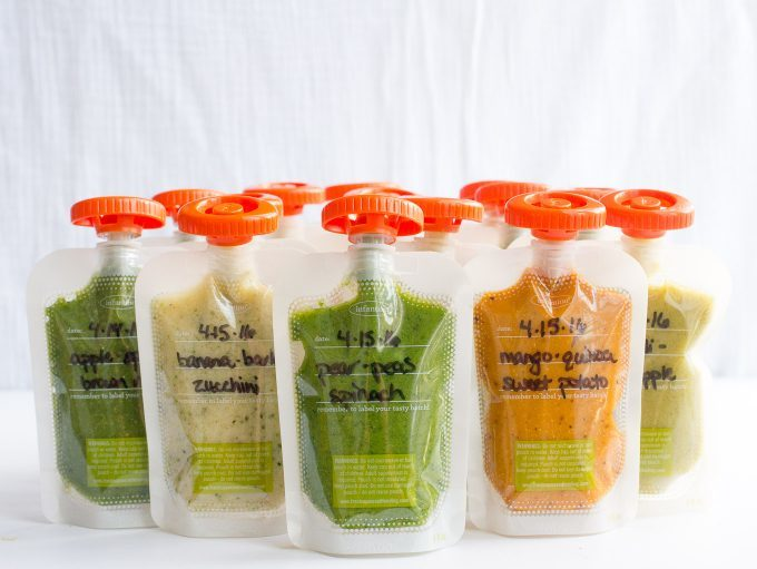A variety of baby food squeeze pouches lined up in plastic pouches with orange tops