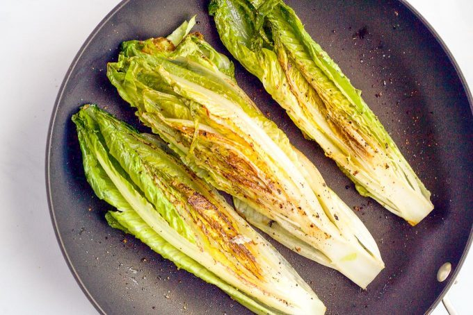 Romaine strips seared in a saute pan with browned spots showing