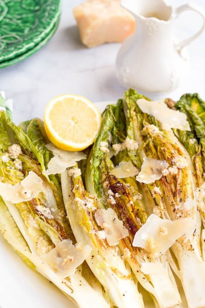 Seared romaine with Parmesan cheese displayed on a white platter