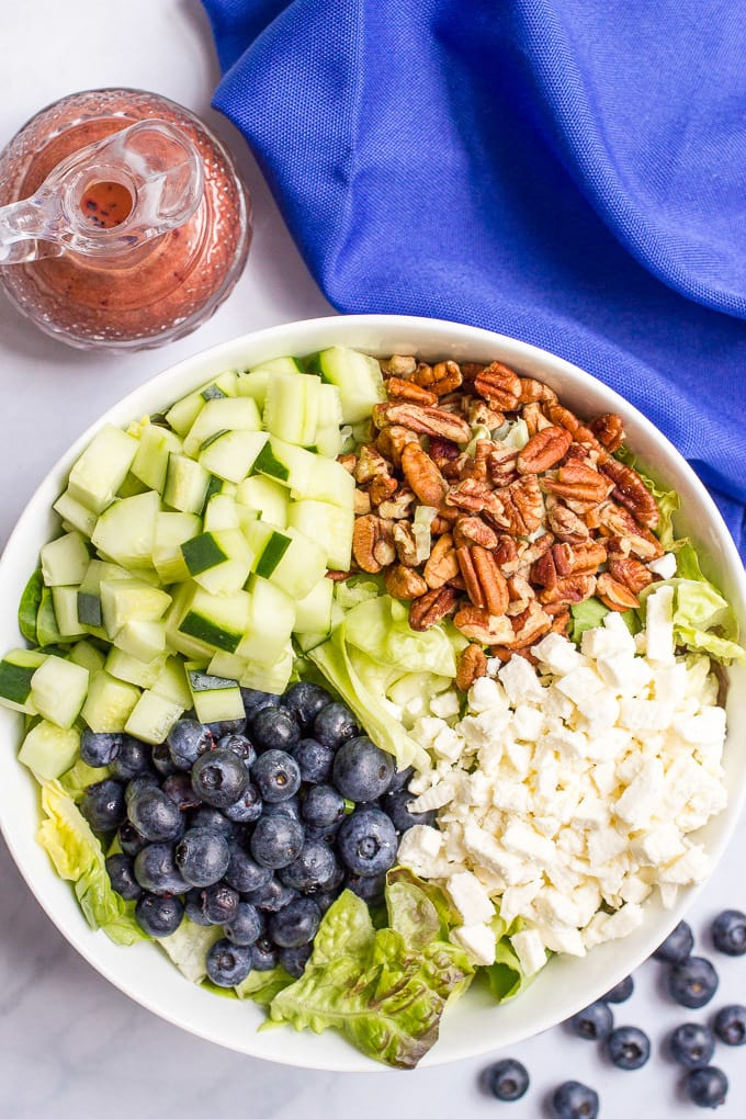 Easy summer salad with cucumbers, blueberries, pecans and feta cheese, topped with a delicious balsamic blueberry vinaigrette! | FamilyFoodontheTable.com