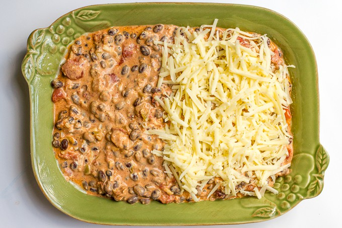 Black bean dip in a green casserole dish topped with shredded cheese