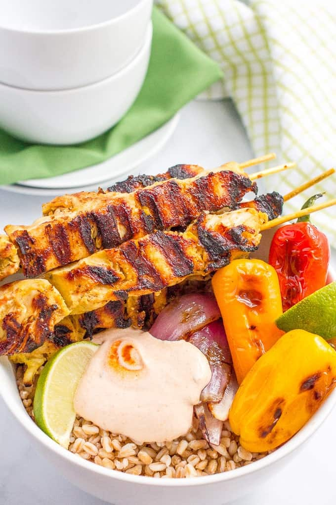 Chili lime chicken kabob grain bowls feature grilled kabobs served in a bowl with chewy farro, roasted peppers and onions, and topped with a creamy, smoky adobo sauce!