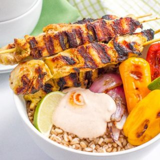Chili lime chicken kabobs in a bowl with farro, peppers and a creamy, smoky adobo sauce - a tasty, healthy summer dinner!