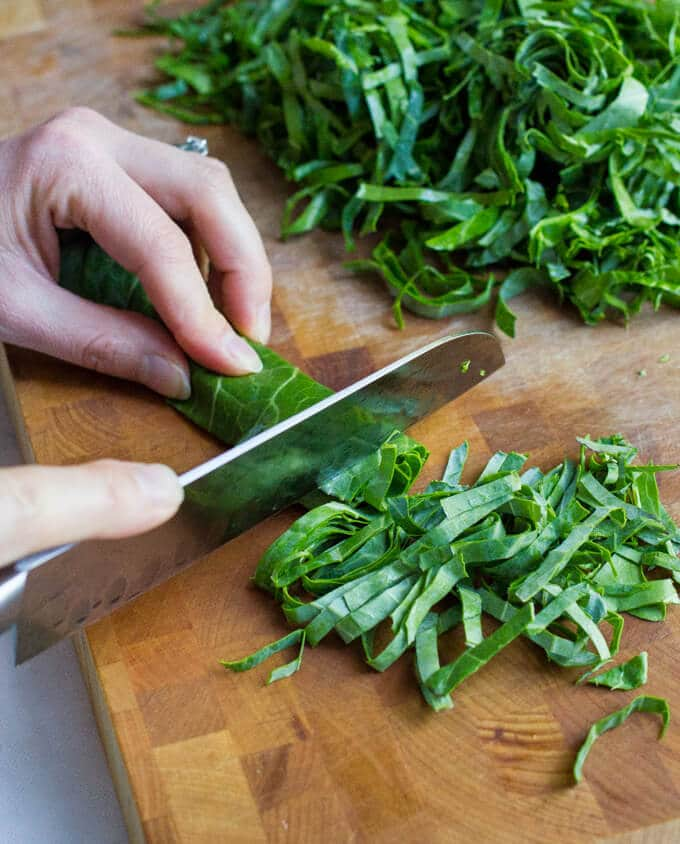 Close up of how to thinly slice and prep collard greens