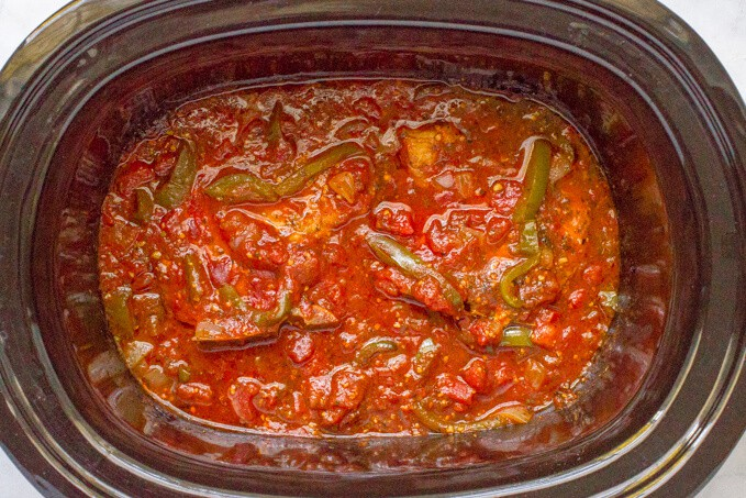 A slow cooker with pork chops and an Italian tomato sauce