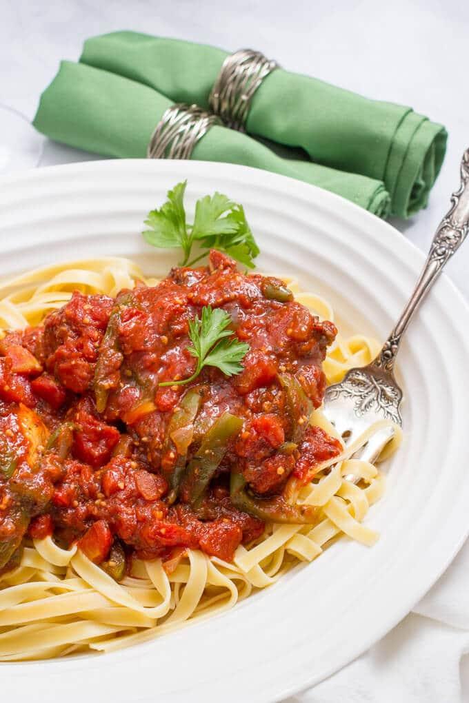 A serving platter with saucy pork chops over pasta noodles