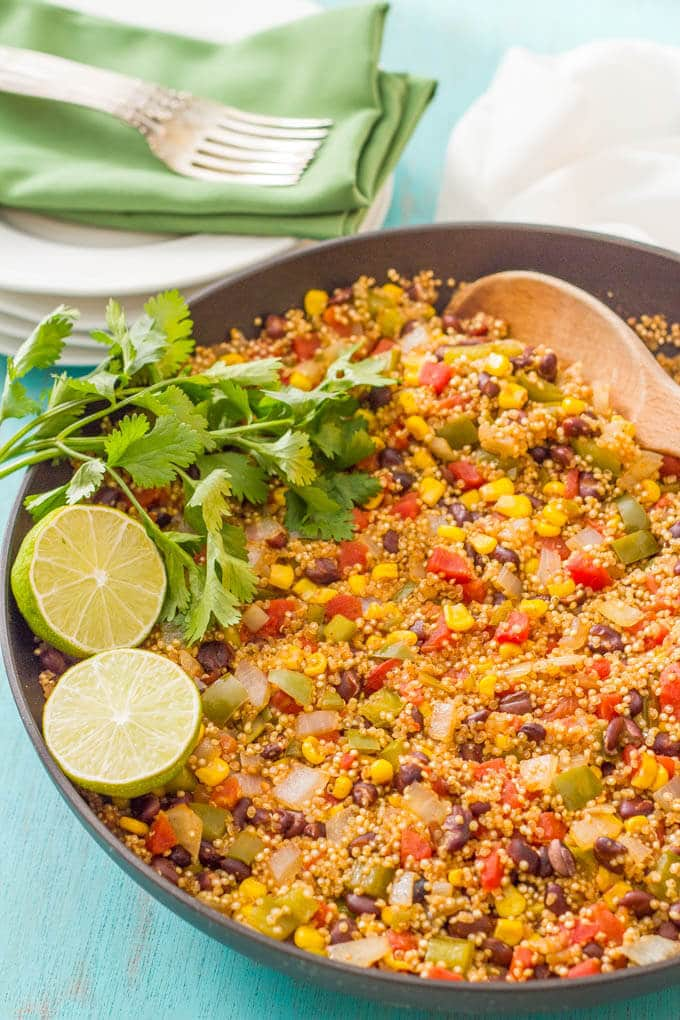 Vegetarian southwest quinoa skillet in the pan with limes and cilantro to garnish
