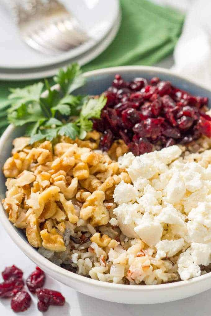Warm wild rice salad with cranberries, pecans and goat cheese is a delicious combination of flavors and textures - perfect for a winter side dish! #wildrice #ricesalad #holidayfood #sidedish