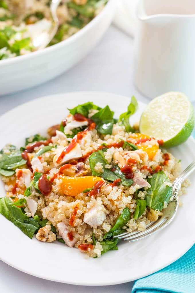Quinoa chicken spinach salad with mandarin oranges, walnuts, served with a honey-lime vinaigrette and sriracha drizzle! | www.familyfoodonthetable.com