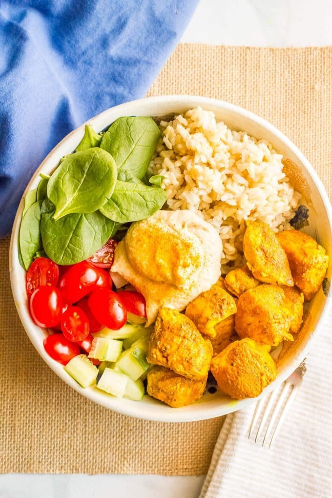 Turmeric chicken bowls with basmati rice, fresh veggies and hummus are a quick, easy and super flavorful meal! Great for meal prepping or throwing together a healthy lunch or dinner! #turmeric #ricebowl #easychickenrecipes