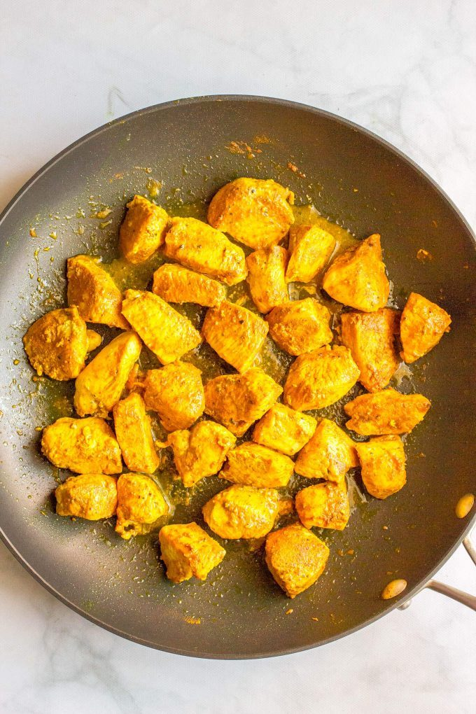 Turmeric chicken cubes cooked in a large skillet